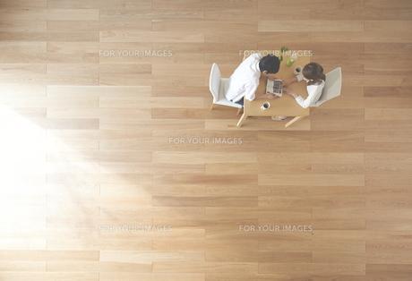 茶色の木の床と本を読む夫婦 FYI01034093