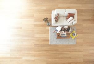 茶色の木の床とパソコンを使う女性達 FYI01034118
