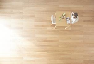 茶色の木の床と本を読む女性 FYI01034119