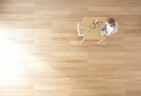 茶色の木の床と本を読む女性 FYI01034138
