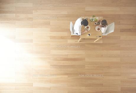 茶色の木の床とデザートを食べる夫婦 FYI01034141