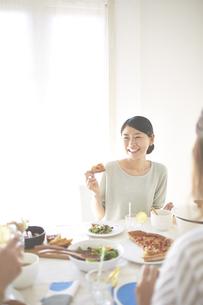 会話を楽しみながらピザを食べる女性 FYI01034193