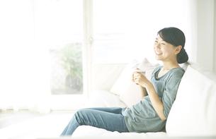 ソファーに座りながら飲み物を飲んでいる女性の素材 [FYI01034212]