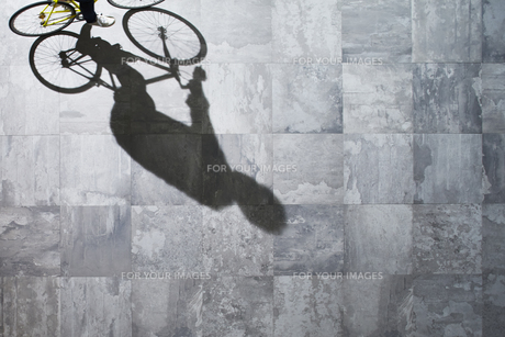光が差し込む石の床を自転車で走る男性 FYI01034215