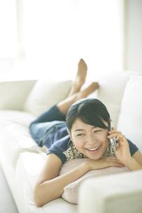 ソファーの上で電話している女性 FYI01034218