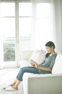 ソファーに座りながら読書している女性 FYI01034225