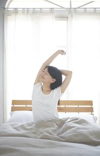 ベッドの上でストレッチをする女性 FYI01034228