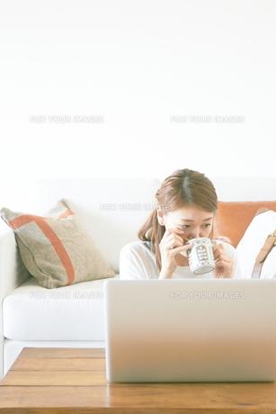 コーヒーを飲みながらパソコンをする女性 FYI01034237