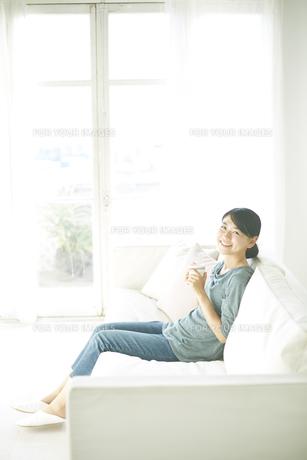 ソファーに座りながら飲み物を飲んでいる女性 FYI01034259