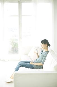 ソファーに座りながら飲み物を飲んでいる女性 FYI01034268