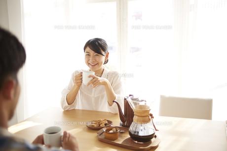 男性とコーヒーを飲みながら会話している女性 FYI01034282