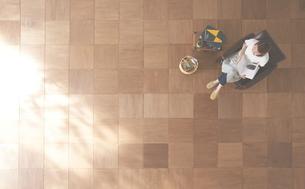 茶色の木の床とソファに座る女性 FYI01034285