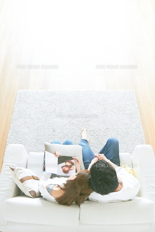 ソファで本を読む夫婦と茶色の木の床 FYI01034322