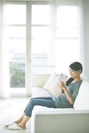 ソファーに座りながら飲み物を飲んでいる女性 FYI01034324