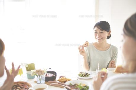 会話を楽しみながらピザを食べる女性 FYI01034346