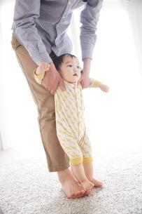 父親と歩く練習をしている赤ちゃん FYI01034507