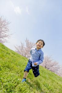 桜の咲く土手で遊ぶ男の子 FYI01075266