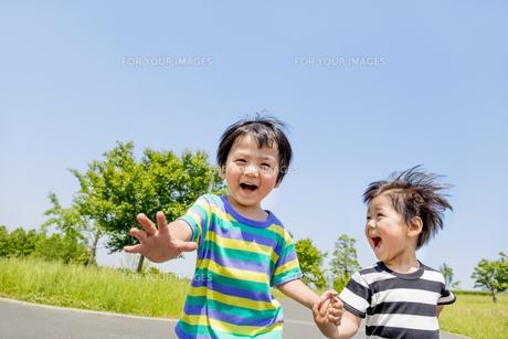 公園を手をつないで走る男の子たち FYI01075470