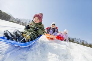 雪の公園でソリ遊びをする子供たち FYI01075526