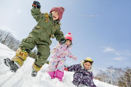 雪の公園でジャンプする子供たち FYI01075530