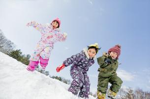 雪の公園でジャンプする子供たち FYI01075540