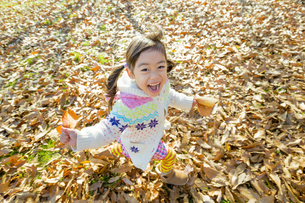 落葉の公園を葉っぱを持って走る女の子 FYI01075605
