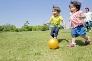 新緑の公園を走る4人家族 FYI01075626
