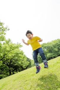 新緑の公園でジャンプをする男の子 FYI01075769