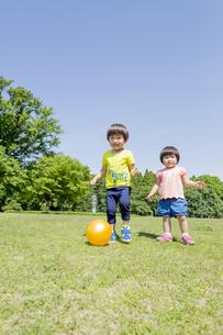 新緑の公園でボールで遊ぶ兄と妹 FYI01075815