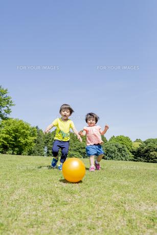 新緑の公園でボールで遊ぶ兄と妹 FYI01075827