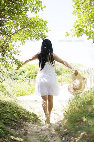 緑の小道で白いワンピースを着て手を広げる女性の後ろ姿 FYI01076545