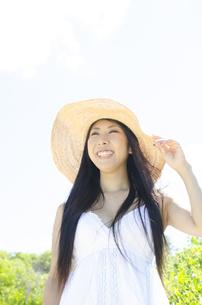 白いワンピースに帽子をかぶって笑うロングヘアの女性 FYI01076547