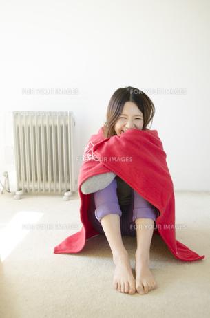 オイルヒーターの前で赤いストールに包まる女性 FYI01076596