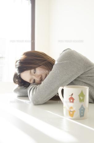 机でうたた寝をする女性とマグカップ FYI01076606