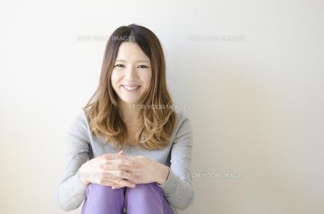 体育座りをして笑顔の女性 FYI01076634