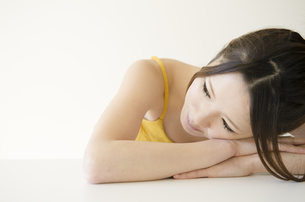 机に腕を組んで顔を乗せる女性 FYI01076674