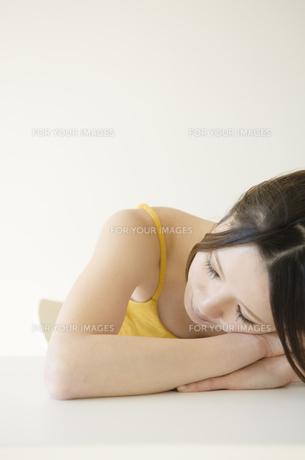 机に腕を組んで顔を乗せる女性 FYI01076675