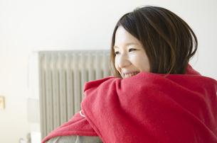 オイルヒーターの前で赤いストールに包まる女性 FYI01076709