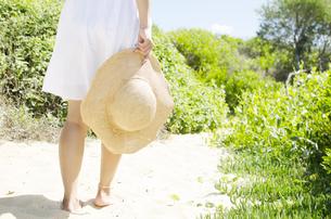 白いスカート姿で帽子を持って砂の上を歩く女性のイメージ FYI01076731