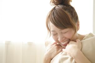 クッションを抱きしめて笑う女性 FYI01076732