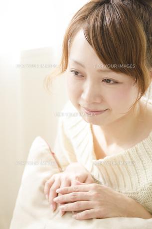 クッションに手を添えて微笑む女性 FYI01076749