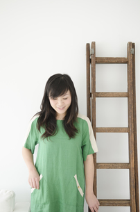はしごの横でうつむく女性 FYI01076750
