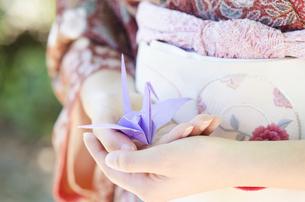 着物姿の女性の手の上に乗せた折り鶴 FYI01076761