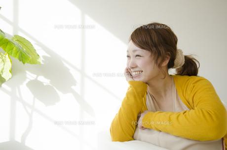 室内で頬杖を付いて微笑む女性 FYI01076782
