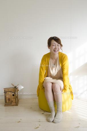 黄色いクッションに座って笑う女性 FYI01076812