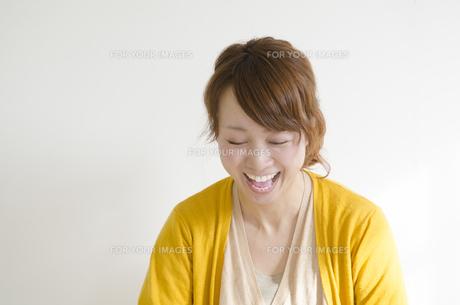 黄色いカーディガンを着て大笑いする女性 FYI01076813