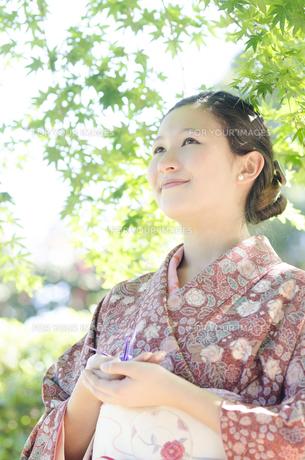 新緑のもみじをバックに微笑む着物姿の女性 FYI01076814
