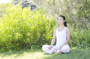 草の上に座ってリラックスする女性 FYI01076831