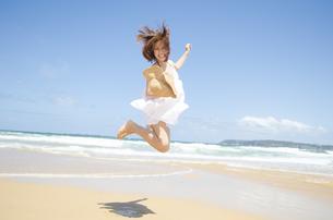 ビーチでジャンプをする女性 FYI01076832