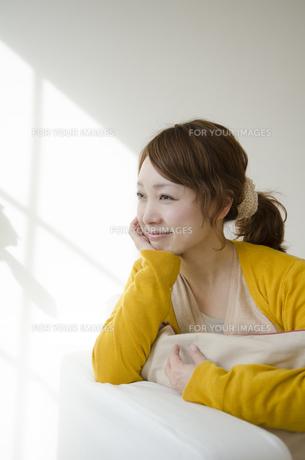 室内で頬杖を付いて微笑む女性 FYI01076861